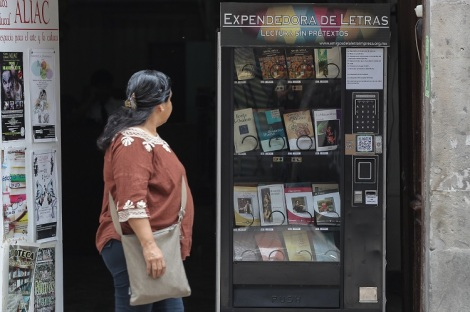 MEX05, CIUDAD DE MÉXICO (MÉXICO), 09/07/2016.- Una mujer observa una máquina expendedora de libros hoy sábado 9 de julio de 2016, en Ciudad de México. Al alcance de unas monedas y de la misma manera en que se adquiere una soda, galletas o golosinas, una persona hambrienta de lectura puede comprar un libro de autores clásicos en una máquina expendedora en el Centro Histórico de la Ciudad de México .EFE/Alex Cruz.